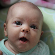 A two month old baby girl makes eye contact with the camera. Photo Tim Clayton