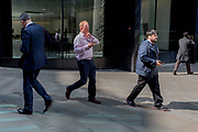 Londoners walk through reflected light at lunchtime on Threadneedle Street in the City of London, the capital's financial district also known as the Square Mile, on 6th April 2017, in London, England.