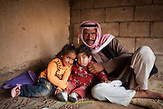 A Bedouin man poses with his children at his home in Rum Village, Wadi Rum, Jordan.