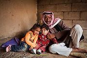 A Bedouin man poses with his children at his home in Rum Village, Wadi Rum, Jordan.