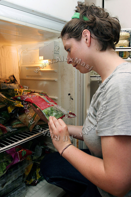 Rachel, 22, is taking some vegetables to cook from the fridge at a Freegan dinner made entirely with food recovered from dumping sites around the island of Manhattan, New York, NY., on Friday, June 23, 2006...Freegans are a community of people who aims at recovering wasted food, books, clothing, office supplies and other items from the refuse of retail stores, frequently discarded in brand new condition. They recover goods not for profit, but to serve their own immediate needs and to share freely with others. According to a study by a USDA-commissioned study by Dr. Timothy Jones at the University of Arizona, half of all food in the United States is wasted at a cost of $100 billion dollars every year. Yet 4.4 million people in the United States alone are classified by the USDA as hungry. Global estimates place the annual rate of starvation deaths at well over 8 million. The massive waste generated in the process fills landfills and consumes land as new landfills are built. This waste stream also pollutes the environment, damages public health as landfills chemicals leak into the ground, and incinerators spew heavy metals back into the atmosphere. Freegans practice strategies for everyday living based on sharing resources, minimizing the detrimental impact of our consumption, and reducing and recovering waste and independence from the profit-driven economy. They are dismayed by the social and ecological costs of an economic model where only profit is valued, at the expense of the environment. In a society that worships competition and self-interest, Freegans advocate living ethical, free, and happy lives centred around community and the notion that a healthy society must function on interdependence. Freegans also believe that people have a right and responsibility to take back control of their time.