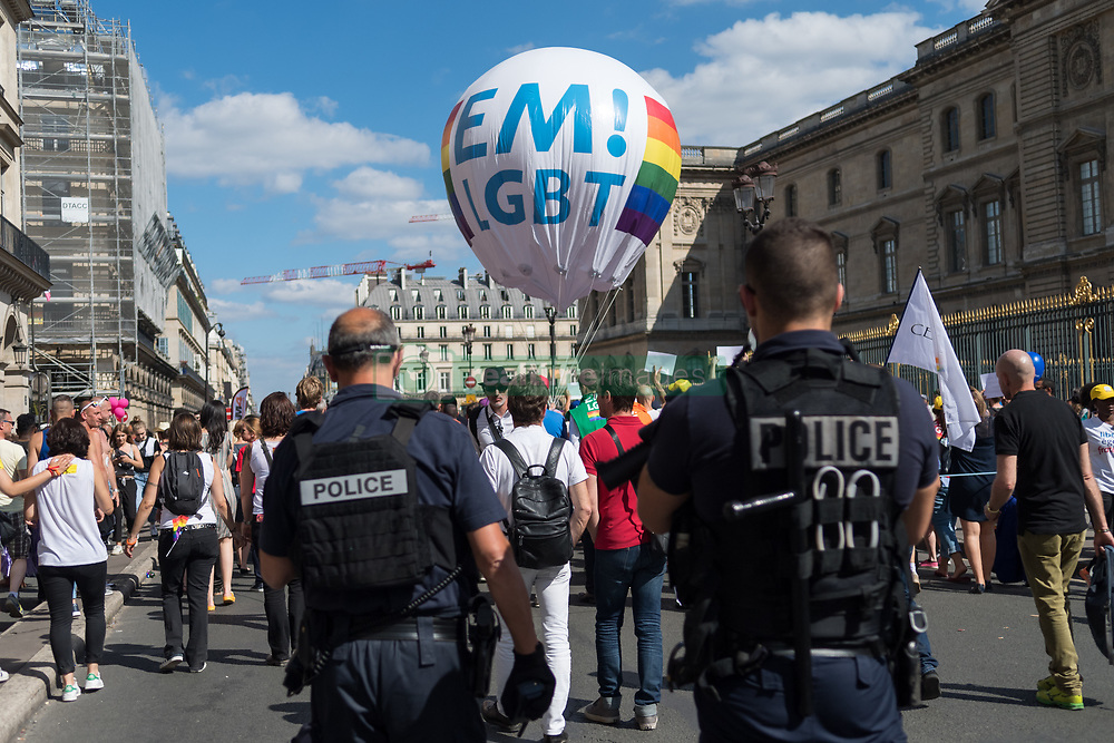 Activists walk beside a security official while taking part in the Gay Pride parade in Paris on June 24, 2017. 2017 marks the 40th anniversary of the first Gay Pride March in the French capital.  (Photo by Julien Mattia/NurPhoto) *** Please Use Credit from Credit Field ***