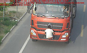 """Truck Driver's Buddy Risks His Life to Cover Up License Plates<br /> <br /> Two Yulin men recently came up with a creative method to obscure their truck's license plates from traffic police cameras. Police spotted the truck on their traffic cameras. The screenshot from the camera shows a man in a white T-shirt crouched at the front of the truck, clinging to the bumper, his body blocking the license plate from view. The vehicle was going at about 20 km per hour.<br /> The photo has since gone viral online. One Netizen commented, """"He is risking his own life to cover up a license plate!""""<br /> Yulin police reported that the incident occurred on the city's Yanhuang Highway. The vehicle was a heavy-duty semi-truck owned by Wubu Taihi County Transport Co., Ltd. The incident in question actually happened on July 28, but was publicized last Wednesday.<br /> Yulin police claim that they were able to identify the vehicle. The driver will be fined 200 RMB and 12 points will be deducted from his license. As of last Thursday, police said that the driver has not yet been punished.<br /> ©Exclusivepix Media"""