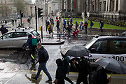 A pedestrian is picked up after falling over in the road during autumnal downpour in Trafalgar Square in central London, on 1st October 2019, in London, England.