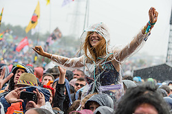 © Licensed to London News Pictures. 26/06/2015. Pilton, UK.  Rain pours down over festival goers at Glastonbury Festival 2015 as they watch Alabama Shakes perform on the Pyramid Stage on Friday Day 3 of the festival.  This years headline acts include Kanye West, The Who and Florence and the Machine, the latter being upgraded in the bill to replace original headline act Foo Fighters.   Photo credit: Richard Isaac/LNP