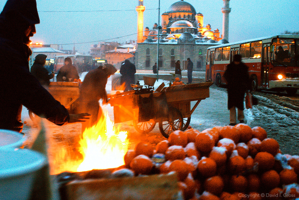 Orange sellers during a snow storm near the Yeni Mosque (Valide Mosque) in Istanbul, Turkey.