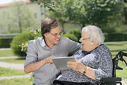 Son with disabled mother using digital tablet, Bavaria, Germany