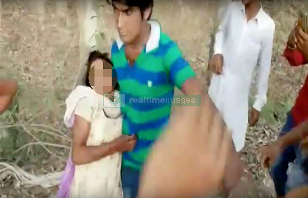 May 29, 2017 - UTTAR PRADESH, INDIA - UTTAR PRADESH, INDIA - MAY, 22, 2017 : A Man (in green T-shirt) trying to help and rescue the girl can be seen pushed back and threatened by the gang of 14, in Rampur district of Uttar Pradesh, India.....The video that has gone viral on internet shows a gang of 14 men riding motorcycles and blocking the way of two girls on a narrow road surrounded by trees. They men can be spotted stalking, pushing, pulling and groping the girls. While the girls can be heard crying for help and struggling to free themselves from their molesters, an onlooker who tried help them and rescue them can be seen pushed back and threatened by the gang.....Pictures supplied by : Cover Asia Press (Credit Image: © Cover Asia Press/Cover Asia via ZUMA Press)