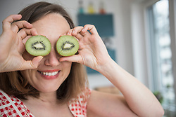 Pregnant woman having fun with pieces of kiwi in the kitchen and smiling, Munich, Bavaria, Germany