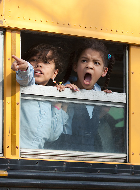 Boston, MA 04/11/2011.Children on a passing school bus react to the scene of a bus crash at Dudley St. and Hampden St. after passengers assaulted the bus driver on Monday afternoon.