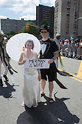 "A man and woman dressed as if bride and groom bear a sign saying ""Merman and wife."" His costume has what may be a formal tail attached to it."