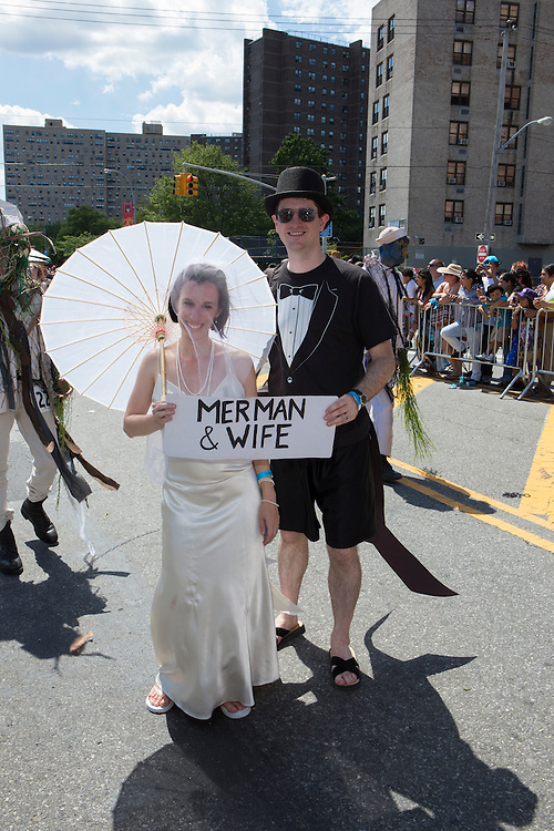 """A man and woman dressed as if bride and groom bear a sign saying """"Merman and wife."""" His costume has what may be a formal tail attached to it."""