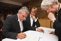 Two men at their Civil Ceremony signing the register, watched by Registrar