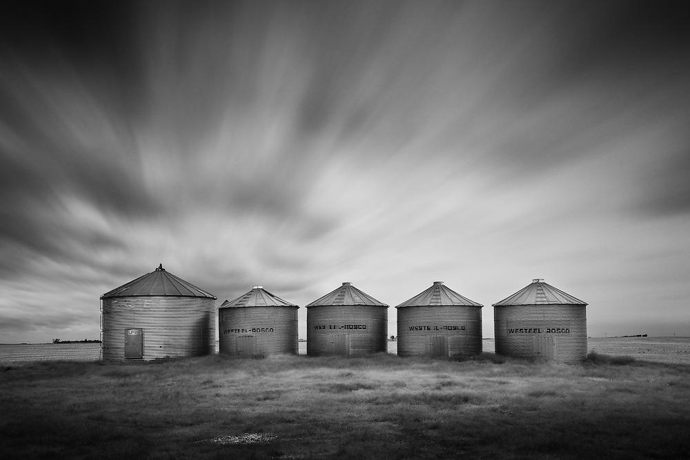 Grain bins overlooking an empty pasture