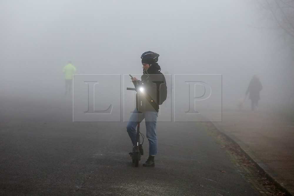 © Licensed to London News Pictures. 08/12/2020. London, UK. A commuter on an electric scooter stops to take a photograph of dense fog in Finsbury Park, north London. Freezing cold and foggy weather is forecast across many parts of the UK. The Met Office has issued a yellow weather warning for the UK unlit 11am for low visibility. Photo credit: Dinendra Haria/LNP