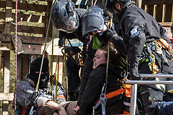 Denham, UK. 22nd March, 2021. Bailiffs from the National Eviction Team (NET) work to remove two anti-HS2 activists who are locked together from a makeshift tower in Denham Country Park where they had been seeking to delay electricity pylon relocation works by Babcock in connection with the high-speed rail project. The activist on the right is calling out to complain about the manner in which she is being touched by one of the male bailiffs.