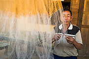 12 MARCH 2013 - ALONG HIGHWAY 13, LAOS:  A fisherman works on his nets on the porch of his home on the side of Highway 13 in rural Laos. The paving of Highway 13 from Vientiane to near the Chinese border has changed the way of life in rural Laos. Villagers near Luang Prabang used to have to take unreliable boats that took three hours round trip to get from the homes to the tourist center of Luang Prabang, now they take a 40 minute round trip bus ride. North of Luang Prabang, paving the highway has been an opportunity for China to use Laos as a transshipping point. Chinese merchandise now goes through Laos to Thailand where it's put on Thai trains and taken to the deep water port east of Bangkok. The Chinese have also expanded their economic empire into Laos. Chinese hotels and businesses are common in northern Laos and in some cities, like Oudomxay, are now up to 40% percent. As the roads are paved, more people move away from their traditional homes in the mountains of Laos and crowd the side of the road living off tourists' and truck drivers.    PHOTO BY JACK KURTZ