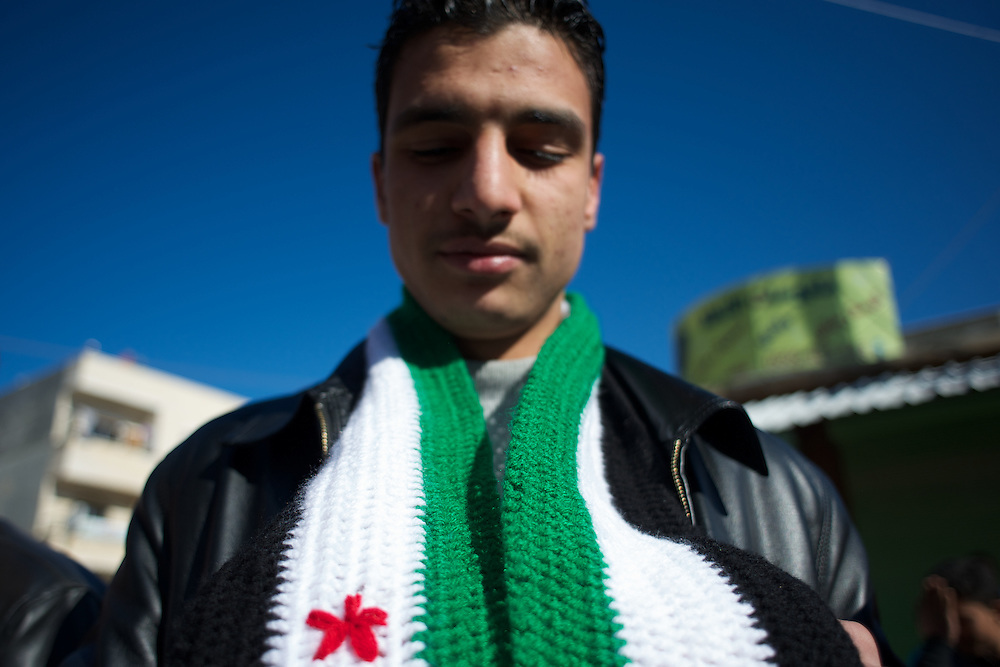 January 20, 2012 - Idleb, Syria: A young man poses holding a scarf with the colors of the Syrian revolutionary flag, during a anti-regime demonstration in central Taftanaz.