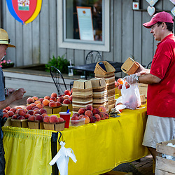 Intercourse, PA – July 20, 2016: A man sells fresh picked peaches at the Kitchen Kettle Village in Intercourse, Lancaster County PA.