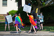 Demonstrators hold signs and a pride flag during the Milton Pride Rally. The I Am Alliance organized the event to show support for the LGBTQ community.