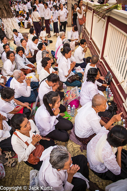"""03 FEBRUARY 2013 - PHNOM PENH, CAMBODIA:   People pray on the sidewalk in front of the National Museum during the final Buddhist chanting service for former Cambodian King Norodom Sihanouk in the crematorium built for the King's funeral at the National Museum in Phnom Penh. Norodom Sihanouk (31 October 1922- 15 October 2012) was the King of Cambodia from 1941 to 1955 and again from 1993 to 2004. He was the effective ruler of Cambodia from 1953 to 1970. After his second abdication in 2004, he was given the honorific of """"The King-Father of Cambodia."""" He served as puppet head of state for the Khmer Rouge government in 1975-1976, before going into exile. Sihanouk's actual period of effective rule over Cambodia was from 9 November 1953, when Cambodia gained its independence from France, until 18 March 1970, when General Lon Nol and the National Assembly deposed him. Upon his final abdication in 2004, the Cambodian throne council appointed Norodom Sihamoni, one of Sihanouk's sons, as the new king. Sihanouk died in Beijing, China, where he was receiving medical care, on Oct. 15, 2012. His cremation will take place on Feb. 4, 2013. Over a million people are expected to attend the service.   PHOTO BY JACK KURTZ"""