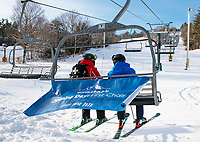"""Kyle Griffin Ski Patrol and Tom Day General Manager ride the """"first chair"""" at Ramrod Quad for opening day at Gunstock Mountain Resort Friday.  (Karen Bobotas Photo/for The Laconia Daily Sun)"""