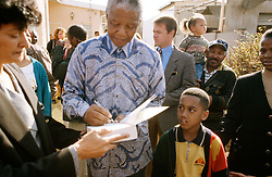 NELSON ROLIHLAHLA MANDELA (July 18, 1918 - December 5, 2013), 95, world renown civil rights activist and world leader. Mandela emerged from prison to become the first black President of South Africa in 1994. As a symbol of peacemaking, he won the 1993 Nobel Peace Prize. Joined his countries anti-apartheid movement in his 20s and then the ANC (African National Congress) in 1942. For next 20 years, he directed a campaign of peaceful, non-violent defiance against the South African government and its racist policies and for his efforts was incarcerated for 27 years. Remained strong and faithful to his cause, thru out his life, of a world of peace. Transforming the world, to make it a better place. PICTURED: South Africa - NELSON MANDELA signs an autograph for a white supporter.  (Credit Image: © Greg Marinovich/ZUMA Wire/ZUMAPRESS.com)