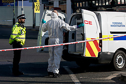 © Licensed to London News Pictures. 27/02/2019. London, UK. Forensic investigators attent the scene outside Ilford Station, where a 20-year-old man was fatally stabbed last night. A murder investigation has been launched. Photo credit: Rob Pinney/LNP