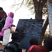 The Stars Foundation visiting Africa Educational Trust (AET) in Somaliland...The small school in Bacado is run by teacher Suleiman Khalip. ..Here Muna from AET watches one of the students at work by the blackboard..The students are children of pastoralists, always move on with their families and the animals they depend on. Suleiman and the school move where the children go and the teaching is done under a tree. When it rains school has to be suspended because the school has no roof and because heavy rain can cut off the children from coming to school because of swelling rivers. The children walk up to 7 km to get to school through the rough terrain, often alone after their parents have initially shown them the way. The children learn to read and write Somali, arithmetic's and Arabic. The schooling is free with all costs covered by African Educational Trust. Because the children are nomads they cannot go to regular school and many are illiterate when they start the course, which is planned to last for 3 years.