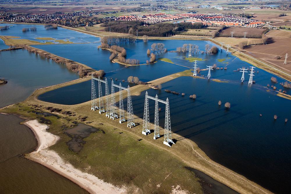 Nederland, Gelderland, Gemeente Nijmegen, 07-03-2010; hoogspanningsmasten aan de oever van de rivier de Waal, de kabels kruisen  de rivier richting elektriciteitscentrale van Electrabel in Nijmegen. Oosterhout aan de horizon..Pylons on the bank of the river Waal, the cables cross the river towards Electrabel power station in Nijmegen .luchtfoto (toeslag), aerial photo (additional fee required).foto/photo Siebe Swart