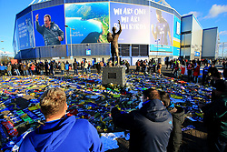 Fans look on at the flowers and scarves placed outside Cardiff City Stadium in tribute to Emiliano Sala during the Premier League match at the Cardiff City Stadium.
