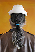 man with ponytail wearing a to small white plaster hat