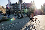 In Amsterdam rijdt een vrouw al bellend op de fiets over de Dam.<br /> <br /> In Amsterdam a woman is crossing the Dam on a bike while phoning.