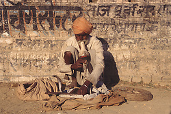 Snake charmer playing pipes and crouching against a wall,