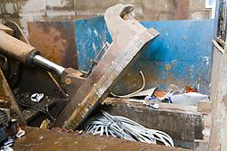 Baler crushing old aluminium quadrant at a metal recycling centre,