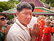 "15 JULY 2011 - PHRA PHUTTHABAT, SARABURI, THAILAND:   A man makes an offering to the monks during the Tak Bat Dok Mai at Wat Phra Phutthabat in Saraburi province of Thailand, Friday, July 15. Wat Phra Phutthabat in Phra Phutthabat, Saraburi, Thailand, is famous for the way it marks the beginning of Vassa, the three-month annual retreat observed by Theravada monks and nuns. The temple is highly revered in Thailand because it houses a footstep of the Buddha. On the first day of Vassa (or Buddhist Lent) people come to the temple to ""make merit"" and present the monks there with dancing lady ginger flowers, which only bloom in the weeks leading up Vassa. They also present monks with candles and wash their feet. During Vassa, monks and nuns remain inside monasteries and temple grounds, devoting their time to intensive meditation and study. Laypeople support the monastic sangha by bringing food, candles and other offerings to temples. Laypeople also often observe Vassa by giving up something, such as smoking or eating meat. For this reason, westerners sometimes call Vassa the ""Buddhist Lent."" The tradition of Vassa began during the life of the Buddha. Most of the time, the first Buddhist monks who followed the Buddha did not stay in one place, but walked from village to village to teach. They begged for their food and often slept outdoors, sheltered only by trees. But during India's summer rainy season living as homeless ascetics became difficult. So, groups of monks would find a place to stay together until the rain stopped, forming a temporary community. Wealthy laypeople sometimes sheltered monks on their estates. Eventually a few of these patrons built permanent houses for monks, which amounted to an early form of monastery.     PHOTO BY JACK KURTZ"
