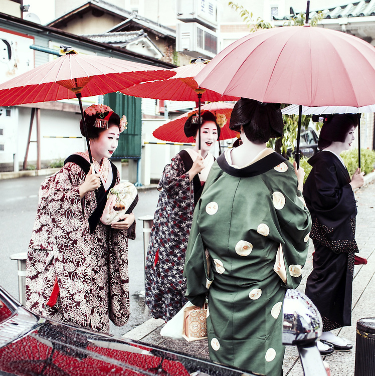 Geishas in a  street of Gion in Kyoto. Gion is an old district of Kyoto with old houses called machilla many of the tea houses and restaurants famous because it is were many Geishas ,called Geikos in  this city, perform every night. For the well conserved architecture the presence of geikos and maikos and the abundance of entertainment it is also one of the main tourist attractions of the city. At the beginning of the century more than 80000 lived in Japan and 800 of those in Gion, nowadays it is believed that this number is less than 1500 all over the country.Around 200 geikos and around 70 maikos  live in Kyoto. In spite of this decline thye last years have seen a resurgence of girls wanting to access this ancient profession that now not only entertains men but also other women families and foreigners that want to take a glimpse in the misterious world of the Geishas.