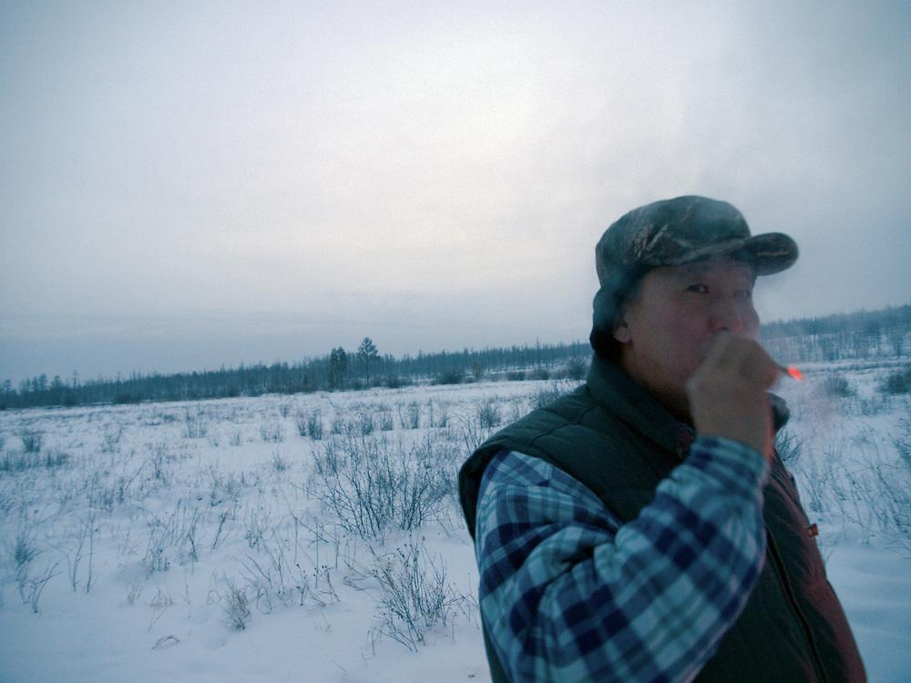 Zigaretten Pause waehrend der Jagd am fruehen Morgen in der sibirischen Taiga - ungefaehr 150 Kilometer entfernt von der sibirischen Stadt Jakutsk. Jakutsk hat 236.000 Einwohner (2005) und ist Hauptstadt der Teilrepublik Sacha (auch Jakutien genannt) im Foederationskreis Russisch-Fernost und liegt am Fluss Lena. Jakutsk ist im Winter eine der kaeltesten Grossstaedte weltweit mit bis zu durchschnittlichen Wintertemperaturen von -40.9 Grad Celsius.<br /> <br /> Cigarette break during an early morning hunting in the Siberian Taiga about 150 km away from the city of Yakutsk. Yakutsk is a city in the Russian Far East, located about 4 degrees (450 km) below the Arctic Circle. It is the capital of the Sakha (Yakutia) Republic (formerly the Yakut Autonomous Soviet Socialist Republic), Russia and a major port on the Lena River. Yakutsk is one of the coldest cities on earth, with winter temperatures averaging -40.9 degrees Celsius.
