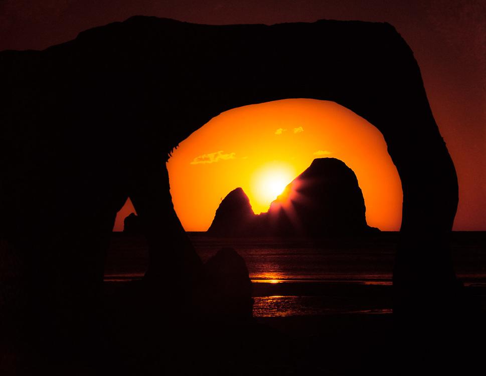 Sunset viewed through a driftwood arch, Pacific Coast, Olympic Natioinal Park, Washington, USA