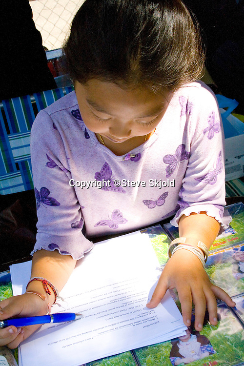 Hmong woman reading instructions at her music CD disk booth. Hmong Sports Festival McMurray Field St Paul Minnesota USA