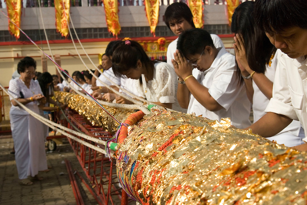 Worshippers pray and place gold leaf before the flag pole raising ceremony at Jui Tui Shine at the Phuket Vegetarian Festival Street Procession, Phuket Town, Thailand.....** The Phuket Vegetarian Festival celebrates the beginning of Taoist Lent, when devout Chinese abstain from eating all meat and other vices.  The festival takes place on the first 9 days of the 9th lunar month of the Chinese calendar.  Everyone dresses in white and shopkeepers set up small alters with offerings of incense, flowers, candles, fruit, and 9 cups of tea to the 9 emperor deities honored by the festival. ....Mediums bring the 9 gods to earth entering a trance state and piercing themselves with all kinds of objects, climbing knife ladders, and walking on hot coals.  The mediums participate in daily processions through town where they stop at the store front alters, drink one of the 9 cups of tea, and offer blessings to the merchants.  The shopkeepers stand in prayer like fashion respecting the mediums that are temporarily possessed by the deity.  The self torture is done to shift evil from individuals to the mediums and bring the community good luck.....Young men carry alters of the deity images though town which culminates at central locations where merchants cover them with huge strands of firecrackers and larger explosives.  The louder and longer blasts are best to drive away evil spirits.  The experience is deafening and engulfs the men and alters in a painful barrage of fire and smoke.  ....Chinese tour groups come to witness since there is no record of this type celebration of Taoist Lent in China.  The festival is believed to have started when a Chinese theatre troupe fell ill for failing to honor the 9 emperor gods of Taoism.  They were quickly cured when they adhered to the 9 day ritual now held each year promoting inner peace, brightness, and proper hygiene.  ..