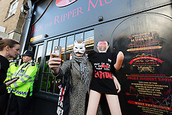"""© Licensed to London News Pictures. 31/10/2015. London, UK. A demonstrator takes a selfie photograph with a blow up doll of museum owner, Mark Palmer-Edgecumbe during a protest outside the Jack the Ripper Museum in Cable Street, Shadwell, east London. The protest is organised by feminist group, The Fourth Wave and attended by Class War and other activists, who are protesting against a Halloween event being held at the museum this weekend, where visitors can take selfie photographs inside the museum with """"Jack the Ripper"""" and some of his female victims played by actors. Photo credit : Vickie Flores/LNP"""