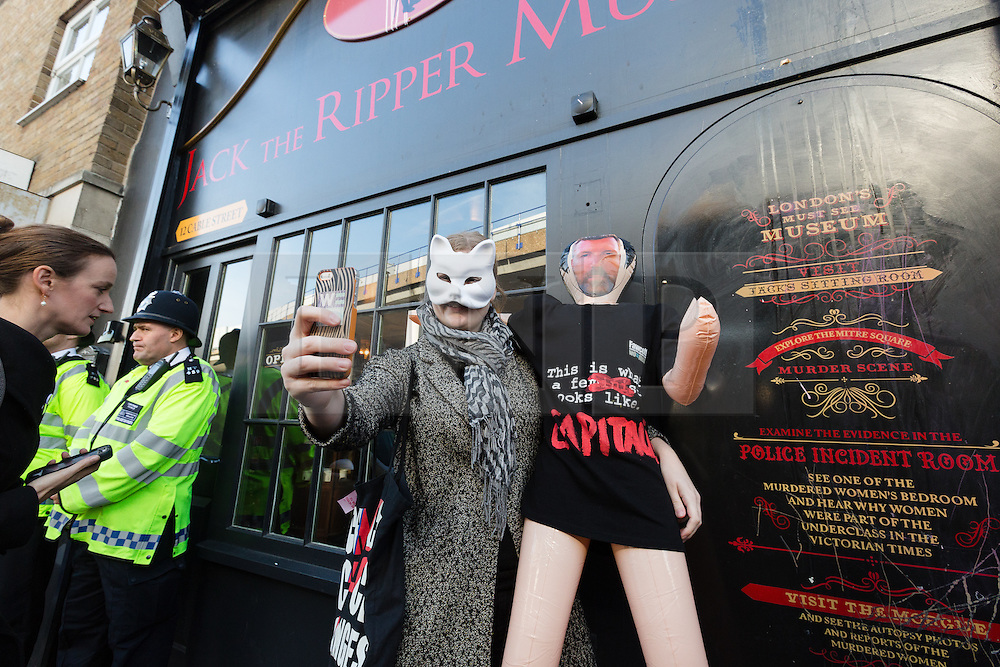 "© Licensed to London News Pictures. 31/10/2015. London, UK. A demonstrator takes a selfie photograph with a blow up doll of museum owner, Mark Palmer-Edgecumbe during a protest outside the Jack the Ripper Museum in Cable Street, Shadwell, east London. The protest is organised by feminist group, The Fourth Wave and attended by Class War and other activists, who are protesting against a Halloween event being held at the museum this weekend, where visitors can take selfie photographs inside the museum with ""Jack the Ripper"" and some of his female victims played by actors. Photo credit : Vickie Flores/LNP"