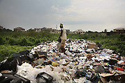 A man is shifting through piles of discarted TVs and other electronic waste in a dump site in the market. Alaba International Market, one of the largest markets for electronic goods in West Africa.  New and old - and a lot of non-working electronic goods such as TVs and computers come in to the market via Lagos harbour from the US, Western Europe and China..Alaba International Market.  <br /> New and old - and a lot of non-working electronic goods such as TVs and computers come in to the market via Lagos harbour from the US, Western Europe and China. This picture is part of an undercover investigation by Greenpeace and Sky News.  A TV-set originally delivered to a municipality-run collecting point in UK for discarded electronic products was tracked and monitored by Greenpeace using a combination of GPS, GSM, and an onboard radiofrequency transmitter placed inside the TV-set.  The TV arrived in Lagos in container no 4629416 and was found in Alaba International Market and bought back by Greenpeace activist. The TV was subsequently brought back to England and used as proof of illegal export of electronic waste. A number of individual are currently on trial in London in connection with illegal exports(Nov 2011)