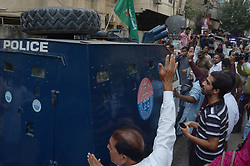 October 5, 2018 - Lahore, Punjab, Pakistan - Pakistani Police officers secure an armored vehicle carrying Pakistani opposition leader Shahbaz Sharif leaving following his court appearance in Lahore. Supporter of opposition Pakistan Muslim League party gathered shouts slogans outside a court during Pakistani opposition leader Shahbaz Sharif leaving following his court appearance. Pakistani court said it would allow the country's anti-graft body to hold opposition leader Shahbaz Sharif for 10 days to interrogate him about alleged links to a multi-million dollar housing scam, his party said. (Credit Image: © Rana Sajid Hussain/Pacific Press via ZUMA Wire)