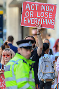 A demonstrator holds up a placard towards the Police officers during the group's 'Impossible Rebellion' series of actions at Oxford Circus in central London, on Wednesday, August 25, 2021. - Climate change demonstrators from environmental activist group Extinction Rebellion continued with their latest round of protests in central London, promising two weeks of disruption. (VX Photo/ Vudi Xhymshiti)
