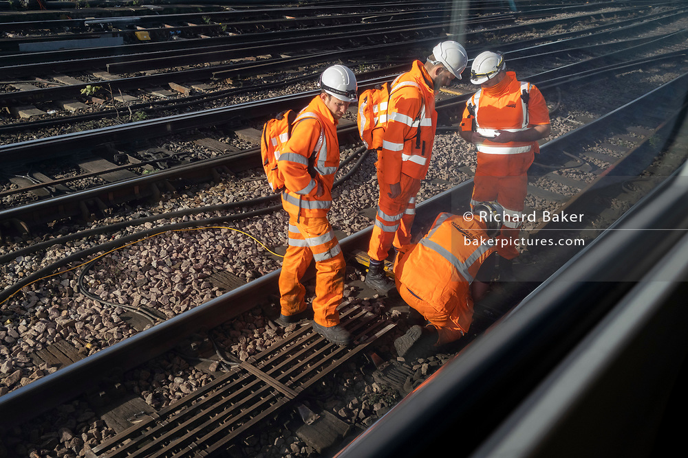 Seen from a passing train carriage window, an engineering work gang inspect rail equipment outside Waterloo mainline station, on 12th November 2020, in London, England.