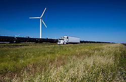 Wind turbine and semi-truck in a grassy field with a clear blue sky.