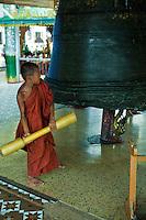 Tiny Buddhist novice monk ringing the temple bell at Shwedagon Pagoda at Yangon - the most sacred pagoda for the Burmese.