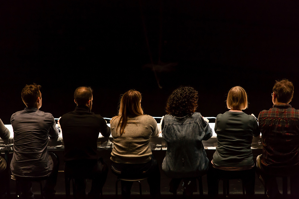 Brooklyn, NY - 11 December 2019. A performance of In Many Hands in BAM's Fishman Space, by Kate McIntosh in collaboration with Arantxa Martinez and Josh Rutter; sound design by John Avery; lighting design by Joëlle Reyms. The piece involves participants sitting at 3 long, narrow tables, with facilitators at each end, and either passing along objects or repeating hand movements in the manner set by a facilitator. Here a long tape is passed down the table.